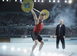 Coach watching male weightlifter squatting barbell overhead in arenaの写真素材 [FYI02853545]