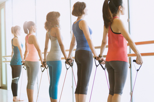 Women exercising with resistance bands at barre in exercise class gym studioの写真素材 [FYI02853553]