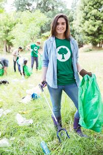 Portrait of smiling environmentalist volunteer picking up trashの写真素材 [FYI02853558]