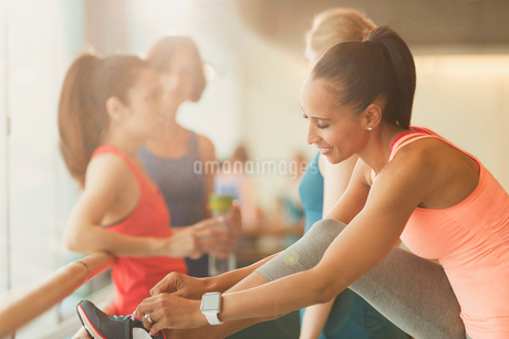 Woman tying shoe at barre in exercise class gym studioの写真素材 [FYI02853568]