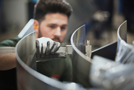 Worker measuring steel with calipers in steel factoryの写真素材 [FYI02853575]