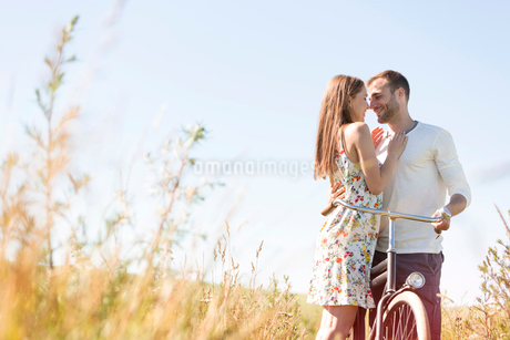 Affectionate young couple with bike hugging in sunny rural fieldの写真素材 [FYI02853598]