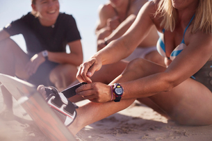 Close up woman fastening kiteboard to feet on beachの写真素材 [FYI02853615]