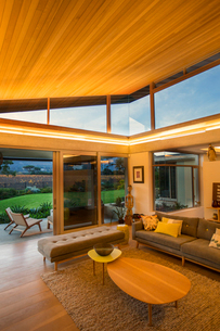 Illuminated wood ceiling over luxury living room open to patioの写真素材 [FYI02853632]