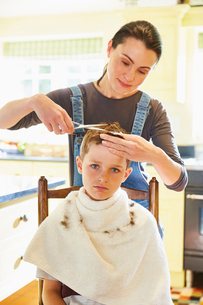 Portrait unhappy boy getting haircut from mother in kitchenの写真素材 [FYI02853638]