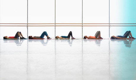 Women resting laying on yoga mats in exercise class gym studioの写真素材 [FYI02853655]