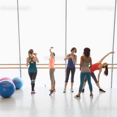 Women stretching and drinking water in exercise class gym studioの写真素材 [FYI02853660]