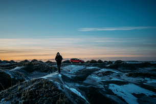 Man walking on icy mounds in remote landscape, Hofn, Icelandの写真素材 [FYI02853662]