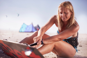 Woman fastening kiteboard to feet on sunny beachの写真素材 [FYI02853666]
