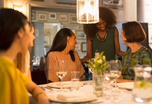 Smiling women friends dining and talking at restaurant tableの写真素材 [FYI02853669]