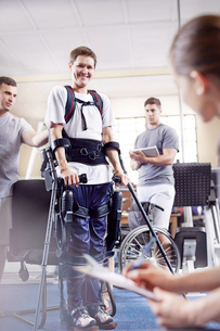 Smiling man with forearm crutches in physical therapyの写真素材 [FYI02853677]