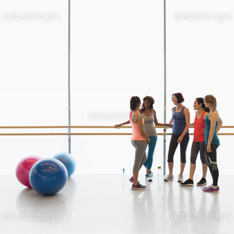 Women talking at barre in exercise class gym studioの写真素材 [FYI02853718]