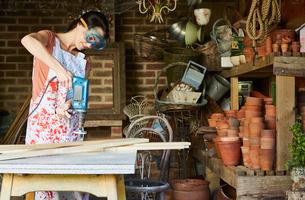 Woman using power sander in workshopの写真素材 [FYI02853730]