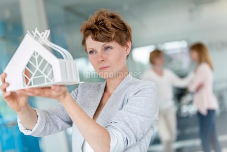 Focused female architect examining model in officeの写真素材 [FYI02853751]