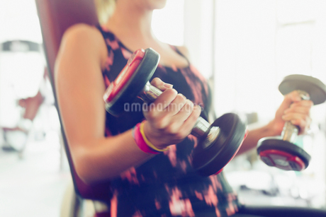 Blurred motion doing dumbbell biceps curls at gymの写真素材 [FYI02853770]