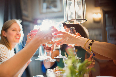 Smiling women friends toasting wine glasses dining at restaurant tableの写真素材 [FYI02853772]