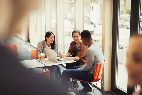 College students using laptop in cafeteriaの写真素材 [FYI02853784]