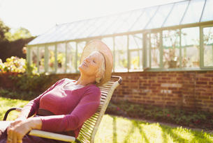 Carefree senior woman relaxing outside sunny greenhouseの写真素材 [FYI02853798]