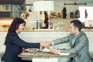 Side view of businessman and businesswoman shaking hands at restaurant tableの写真素材 [FYI02853842]