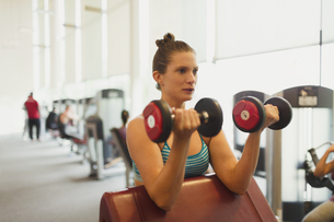 Focused woman doing dumbbell biceps curls at gymの写真素材 [FYI02853846]