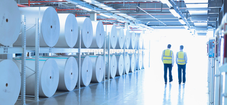 Workers in reflective clothing walking along large paper spools in printing plantの写真素材 [FYI02853854]