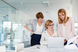 Female architects at laptop reviewing blueprints in conference room meetingの写真素材 [FYI02853894]