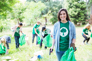 Portrait of smiling environmentalist volunteer picking up trashの写真素材 [FYI02853899]