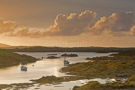 Tranquil sunset view fishing boats on lake, Harris, Outer Hebridesの写真素材 [FYI02853956]