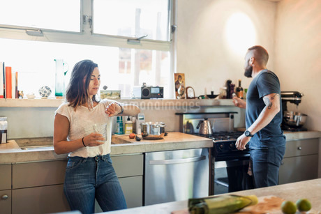 Woman checking time while man looking through window in kitchenの写真素材 [FYI02853990]