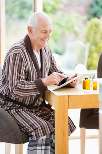 Older man using tablet computer at tableの写真素材 [FYI02854044]