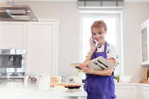 Female caterer with cookbook baking, talking on cell phone in kitchenの写真素材 [FYI02854078]