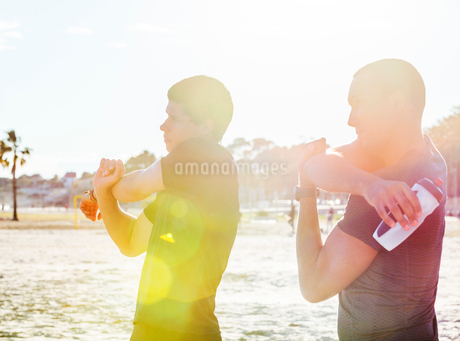 Male runners stretching arms on sunny beachの写真素材 [FYI02854091]