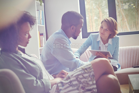 Female therapist with digital tablet comforting man in couples therapy sessionの写真素材 [FYI02854102]
