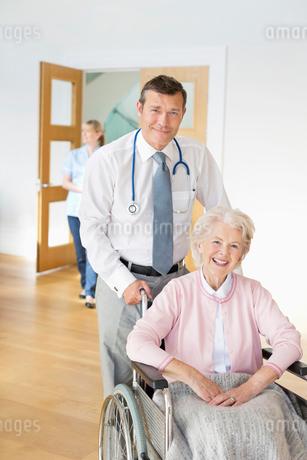 Doctor pushing older patient in wheelchairの写真素材 [FYI02854131]