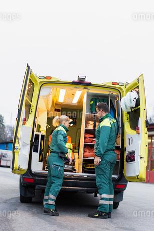 Sweden, Sodermanland, Tumba, Two paramedics next to ambulanceの写真素材 [FYI02854135]