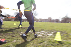 People racing, doing team building exercise in sunny parkの写真素材 [FYI02854139]