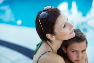 Pensive woman sitting by swimming pool with daughterの写真素材 [FYI02854146]