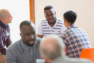 Men talking and listening in group therapyの写真素材 [FYI02854161]