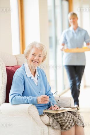 Older woman smiling in armchairの写真素材 [FYI02854236]