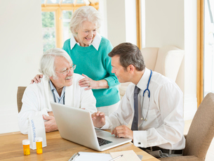 Doctor speaking with older patients at house callの写真素材 [FYI02854254]
