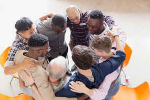 Men hugging in huddle in group therapyの写真素材 [FYI02854282]