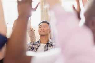 Serene man praying with arms raised in prayer groupの写真素材 [FYI02854295]