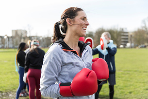 Smiling, confident woman boxing in parkの写真素材 [FYI02854307]
