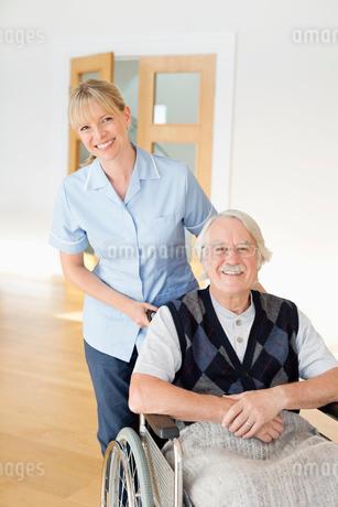Caregiver pushing older man in wheelchairの写真素材 [FYI02854308]