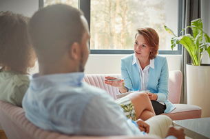 Therapist talking to couple in couples therapy sessionの写真素材 [FYI02854318]