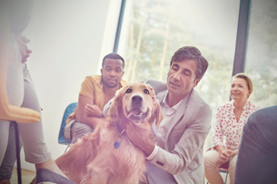 Man petting dog in group therapy sessionの写真素材 [FYI02854382]