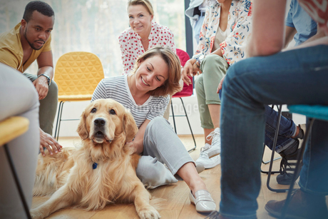 Woman petting dog in group therapy sessionの写真素材 [FYI02854392]