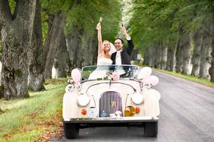 Sweden, Vastra Gotaland, Naas, Bride and groom in carの写真素材 [FYI02854404]