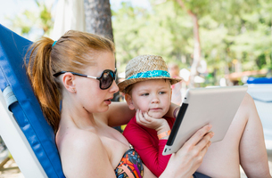 Turkey, Mugla, Marmaris, Mother and son (4-5) using tablet on summer holidayの写真素材 [FYI02854405]