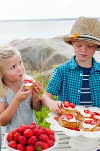 Sweden, Uppland, Roslagen, Children (6-7, 8-9) eating strawberry dessert outdoorsの写真素材 [FYI02854408]